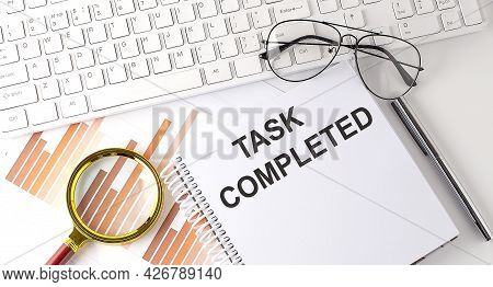 Task Completed Text Written On Notebook With Keyboard, Chart,and Glasses