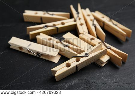 Wooden Clothespins On Black Slate Table, Closeup