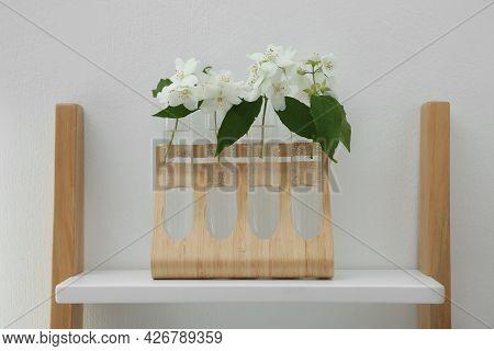 Beautiful Jasmine Flowers On Shelving Unit Near Light Wall