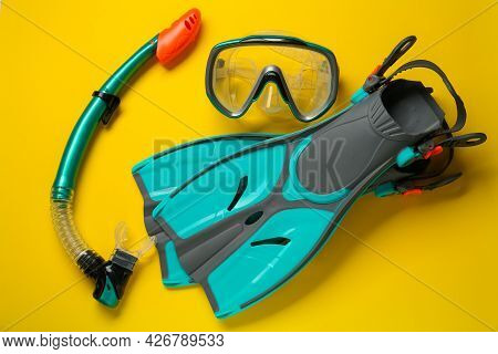 Pair Of Turquoise Flippers And Mask On Yellow Background, Flat Lay