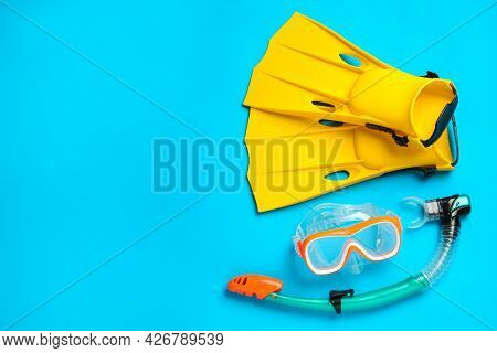 Pair Of Yellow Flippers And Mask On Light Blue Background, Flat Lay. Space For Text