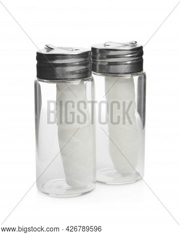 Rolls Of Natural Organic Dental Floss In Jars On White Background