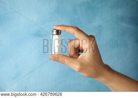 Woman Holding Glass Jar With Biodegradable Dental Floss Against Light Blue Background, Closeup