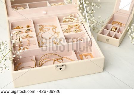 Jewelry Boxes With Different Elegant Bijouterie And Flowers On White Table