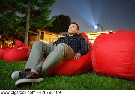 Mature Man Laying On Pillow On Grass And Watching Movie At Outdoor Cinema In Public Park. Perfect Sp