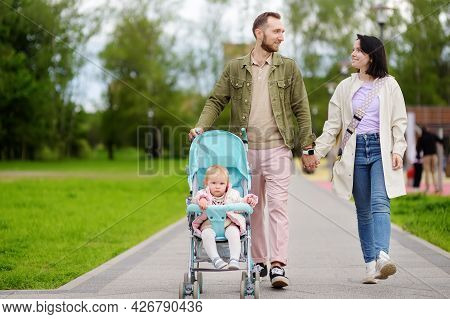 Adorable Toddler Girl Is Riding Into Baby Stroller During Walk With Her Young Loving Parents . Activ