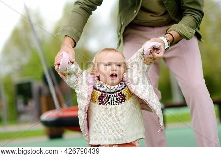 Cute Toddler Girl Having Fun On Outdoor Playground. Young Father Is Teaching His Little Daughter To