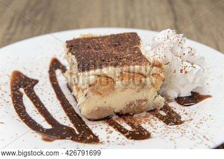 Sweet Dessert On A Decorated Plate Of Tiramisu Cake To Enjoy After A Meal.