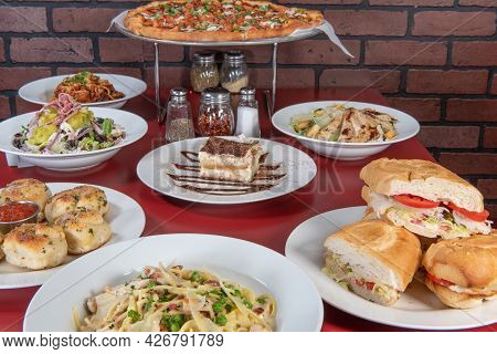 Pizzaria Feast Of A Full Table Of Food Consisting Of Pizza, Pasta, Sandwiches, Dessert, And Salad To