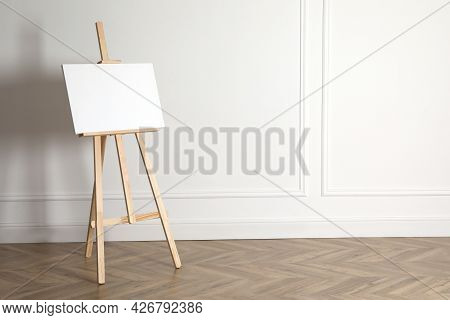 Wooden Easel With Blank Canvas Near Light Wall. Space For Text