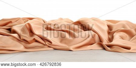Beautiful Peach Silk On Wooden Table Against White Background