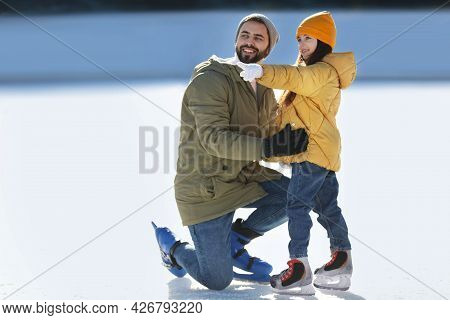 Father And Daughter Spending Time Together At Outdoor Ice Skating Rink