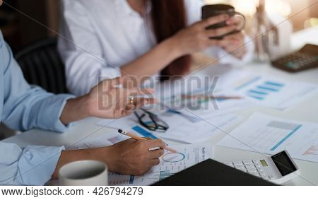 Businesswoman Holding Pens And Holding Graph Paper Are Meeting To Plan Sales To Meet Targets Set In