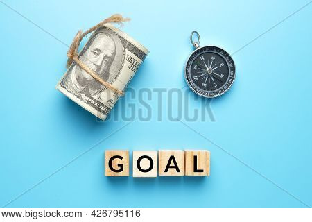 Wooden Block Written Goal, Fake Money And Compass. Financial Goal And Plan Concept