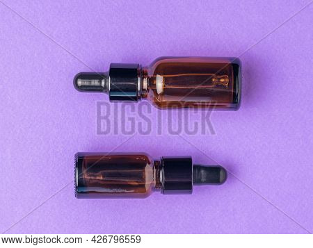 Two Medical Bottles With A Pipette On A Purple Background. The Concept Of Treatment And Body Care Us