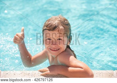 Kid Boy Swim In Swimming Pool With Thumbs Up. Happy Little Kid Boy Playing With In Outdoor Swimming