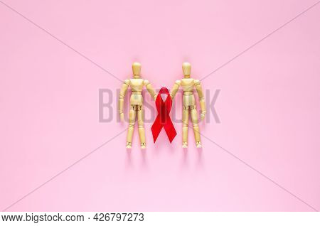 Two Male Wooden Model Holding Red Ribbon For Minimal Safe Sex, World Sexual Health And Aids Day Conc