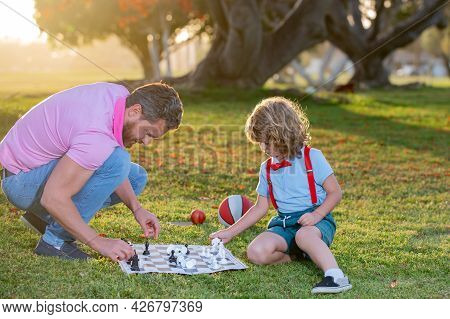 Happy Family Outdoor. Clever Concentrated And Thinking Smart Child Playing Chess. Father And Son Pla