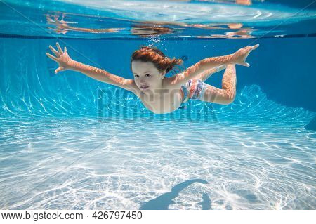 Child Swim Underwater In Pool. Kid Boy Swimming And Diving Underwater In Pool. Summer Family Summer
