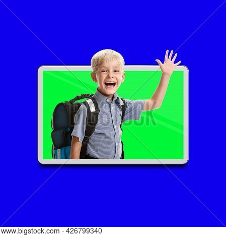 Cute Schoolboy Studying Via Internet With Modern Digital Pad Concept, Blue Chroma Key On The Backgro