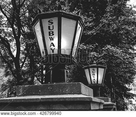 Side Angle Shot Of An Old Fashioned Lamp On A Short Pole Near Another Lamp With The Inscription