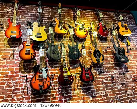 A Variety Of Electric Guitars And Bass Guitars With Price Tags, Hanging On A Brick Wall In Guitar Ce
