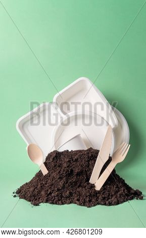 Various Single-use Tableware Non-plastic Alternative In Ground Heap On Green Background, Vertical. W