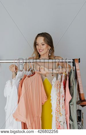 Happy woman in a yellow dress organizing a dress on a garment rack