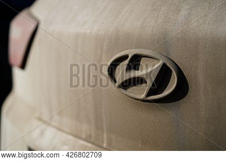 Irkutsk, Russia - July 10 2021: Close Up Dirty Dusty Hyundai Symbol On Back Of White Car. Do Not For