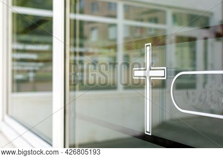 Closeup Of A White Cross On A Window. Church In The Background.funeral House Summer Day After Covid-