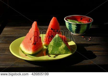 Three Beautiful Triangular Slices Of Watermelon With Juicy Red Pulp And Black Seeds On A Green Platt