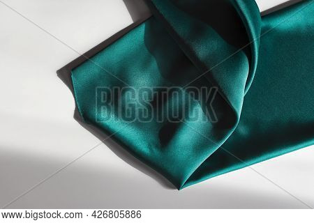 Blue-green Satin Fabric. Smooth Silk Fabric Cut Off On The Table. Shiny Soft Folds In Selective Focu