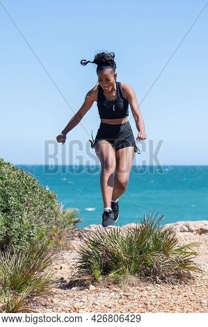 Strong Afro American Woman Vigorously Jumping Over A Plant: Selective Focus. Exercise Concept.