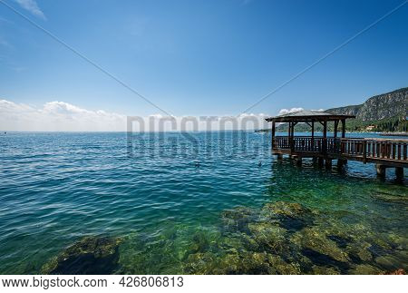 Wooden Pier With Roof On Lake Garda (lago Di Garda) In Front Of The Small Garda Town, Bay With The H