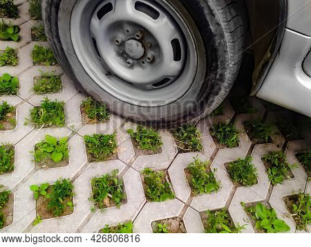 Car Wheel On Eco Friendly Parking Lot Made Of Concrete With Cells For Grass Germination, Copy Space.