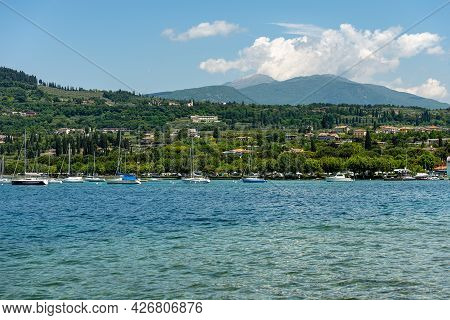 Coast Of Lake Garda (lago Di Garda) In Front Of The Small Village Of Bardolino With Moored Sailboats