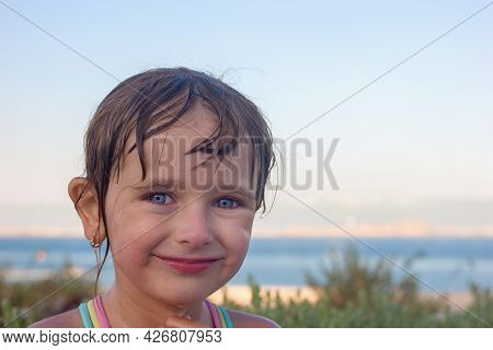 Portrait Of A Beautiful Smiling Little Girl With Wet Hair On The Background Of The Sky And The Sea C