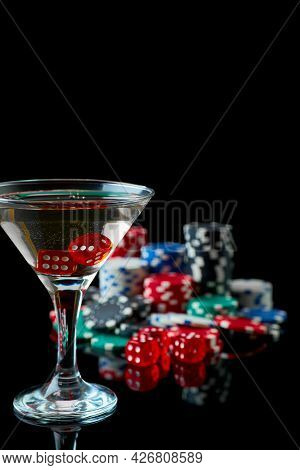 Stack Of Casino Gambling Chips, Glass Of Martini Vermouth And Red Dices Isolated On Reflective Black