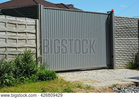 A Close-up Of A Gray Metal Sliding Automatic Gate, Sliding Driveway Gate With A Concrete Fence.