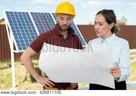 Project manager and contractor discussing maintenance of solar panels, green energy concept