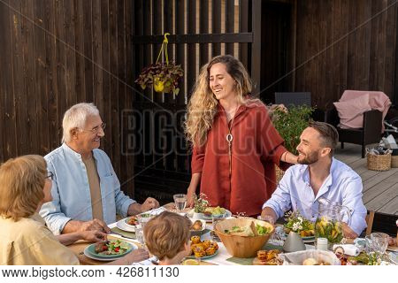 Beautiful young woman with long curly hair giving toast at dinner party with her family