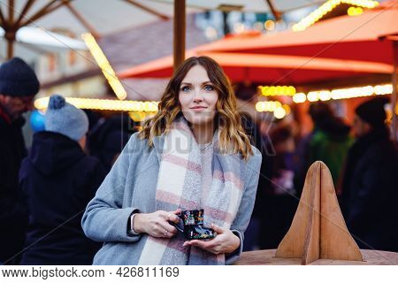 Beautiful Young Woman Drinking Hot Punch, Mulled Wine On German Christmas Market. Happy Girl In Wint
