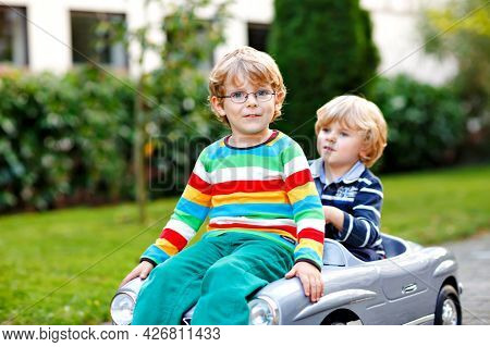 Two Little Preschool Boys Playing With Big Old Toy Car In Summer Garden, Outdoors. Happy Children Pl