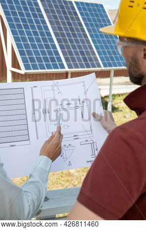 Head engineer and contractor discussing construction plan of house roof with solar panels