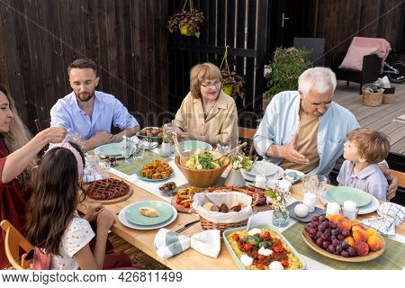 Grandfather talking to little grandson at family reunion dinner