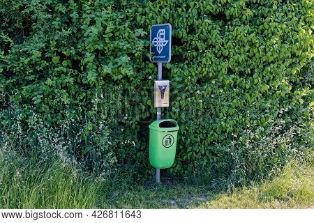 Elgg, Switzerland June 17, 2021: Nature Protection Area, Green Waste Bucket With Dog Waste Bag And N
