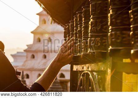 Close-up Of Hand Turning Tibetan Prayer Wheels At Swayambhunath Temple Or Monkey Temple, Kathmandu,