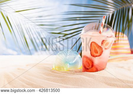 Cold Fresh Pink Cocktail With Ice, Straw In Plastic Mug In Sunlight On Tropical Beach With Ocean Vie