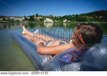 A Little Cute Girl In A Swimsuit Swims On An Inflatable Mattress On A Blue Career Lake.