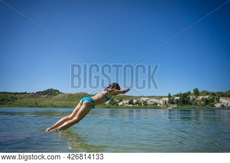 A Little Cute Girl In A Swimsuit Jumps Into The Blue Water Of A Career Lake.